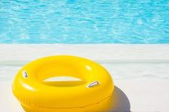 Flotador amarillo de la piscina en la piscina Imagen de archivo libre de regalías