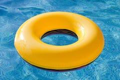 Flotador amarillo que flota en la piscina Imágenes de archivo libres de regalías