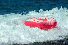 Flotador asperjado inconformista del buñuelo en ondas del mar Fondo del verano fotos de archivo libres de regalías