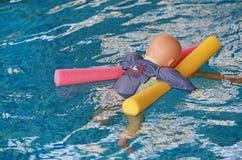 Flotador de entrenamiento de ahogamiento simulado de la muñeca en la piscina con los tallarines imagen de archivo libre de regalías