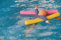 Flotador de entrenamiento de ahogamiento simulado de la muñeca en la piscina con los tallarines imagen de archivo