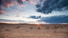 Flotador de las nubes sobre el desierto en la puesta del sol almacen de video