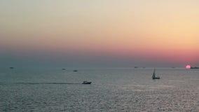 Flotador de los yates en la puesta del sol por el mar almacen de video