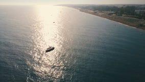 Flotador del barco de la velocidad de la visión aérea cerca de la costa en agua tranquila en un día soleado Reflexión de Sun ence almacen de video