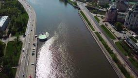 Flotador del barco de placer o el ir rio abajo en ciudad o megapolis Vista aérea del barco azul y blanco con la gente almacen de video