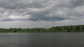 Flotador gris de las nubes de tormenta sobre el lago Lluvia en el río La tormenta en el lago El tiempo dado vuelta malo en el ver almacen de metraje de vídeo