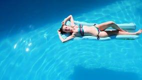 Flotador milenario de la muchacha en la piscina, festival, hotel, playa, evento que sonríe con las gafas de sol encendido durante metrajes