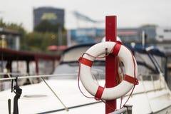 Flotador rojo delante de un puerto deportivo Imagenes de archivo
