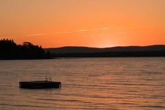 Flotador y lago que nadan en Vermont en la puesta del sol foto de archivo libre de regalías