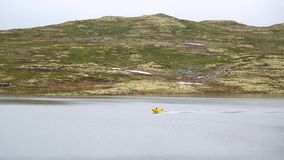 Flotadores amarillos del barco de motor en un lago en Noruega metrajes