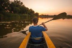 Flotadores del hombre en el kajak deportes acuáticos de la puesta del sol del hombre del kajak fotografía de archivo
