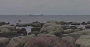 Flotadores pedregosos del buque de carga de la orilla de mar Báltico en el horizonte en tiempo nublado del otoño metrajes