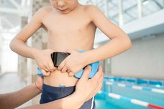 Flotation belt for kids. Close-up of concentrated boy putting on flotation device supported by parent in indoor pool, learning to swim concept royalty free stock photos