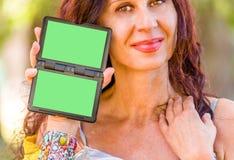 Flott brasiliansk kvinna som rymmer den gröna skärmen royaltyfri fotografi
