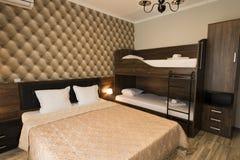 Flott design för hotellsovruminre Stor säng, brits-sängar Familjrum med brunt färgsignalmöblemang arkivbild