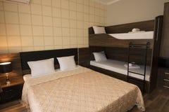 Flott design för hotellsovruminre Stor säng, brits-sängar Familjrum med brunt färgsignalmöblemang royaltyfri foto