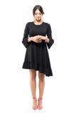 Flott elegant kvinna i svart klänninganseende med knäppte fast händer som ner ser arkivfoto