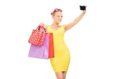 Flott flicka med shoppingpåsar som tar en selfie royaltyfri foto