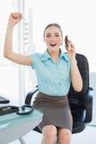 Flott gladlynt affärskvinna på telefonbifallet med lyftta armar fotografering för bildbyråer
