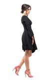 Flott glamourkvinna i svart klänning och rosa sandaler som går och ser ner sidosikt royaltyfria foton