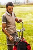 Flott golfspelare som väljer en klubba Arkivfoton
