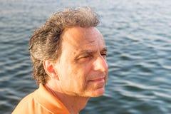 Flott hög idrottsman som framme tänker av havet arkivfoto