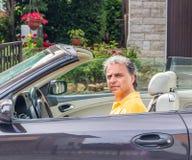 Flott hög idrottsman som kör cabrioletbilen royaltyfri foto