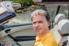 Flott hög idrottsman som kör cabrioletbilen arkivbild