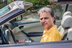 Flott hög idrottsman som kör cabrioletbilen fotografering för bildbyråer