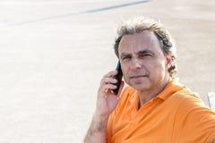 Flott hög idrottsman som talar på en mobiltelefon royaltyfri bild