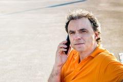 Flott hög idrottsman som talar på en mobiltelefon arkivbilder