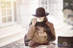 Flott kafé för kvinnasammanträde utomhus med mobiltelefonen arkivfoto