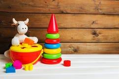 Flott ko och plast- staplande leksak på vit träbakgrund färgrik pyramid Färgrik sorterare royaltyfri foto