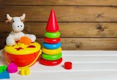 Flott ko och plast- staplande leksak på vit träbakgrund färgrik pyramid Färgrik sorterare royaltyfria foton