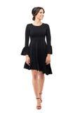 Flott kvinna för lycklig glamour i svart klänning som går och ser le bort royaltyfri foto