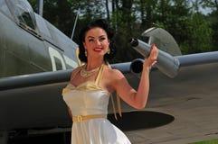Flott kvinna med brittiskt WWII-flygplan royaltyfri bild