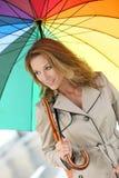 Flott kvinna under det färgade paraplyet för regnbåge arkivfoto