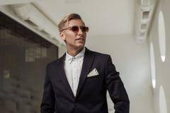 Flott man i dräkt och solglasögon royaltyfri foto