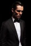 Flott man i smokingen som ser bort i mörk studio royaltyfria foton
