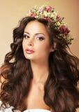 Flott modemodell med den perfekta Flossy bruna hår och kransen av blommor royaltyfri bild