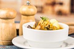 Flott portion av potatissoppa med kött och vegatables som tjänas som i vita bunkar som sitter på tabellen, blå bordduk som är sal royaltyfri bild
