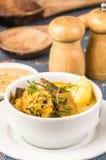 Flott portion av potatissoppa med kött och vegatables som tjänas som i vita bunkar som sitter på tabellen, blå bordduk som är sal royaltyfri fotografi