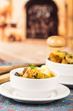 Flott portion av potatissoppa med kött och vegatables som tjänas som i vita bunkar som sitter på tabellen, blå bordduk som är sal arkivbild