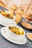 Flott portion av potatissoppa med kött och vegatables som tjänas som i vita bunkar som sitter på tabellen, blå bordduk som är sal royaltyfri foto