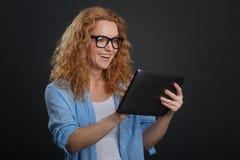 Flott smart dam som är upphetsad om hennes upptäckt direktanslutet arkivbild