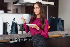 Flott ung latinsk kvinna som dricker kaffeanseende i köket som kopplar av, når att ha shoppat royaltyfri bild