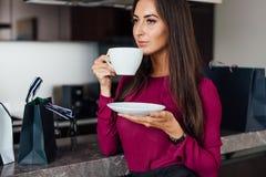 Flott ung latinsk kvinna som dricker kaffeanseende i köket som kopplar av, når att ha shoppat arkivbild
