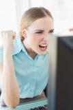 Flott upphetsad affärskvinna som framme sitter av datoren arkivfoto