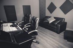 Flott yrkesmässig aktivering för inspelningstudio, stort skrivbord med den blandande konsolen och två stolar, fönster för det rös Arkivfoto