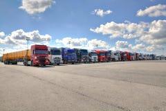 Flotta av lastbilar med släpet i borggård av logistikterminalen arkivfoto